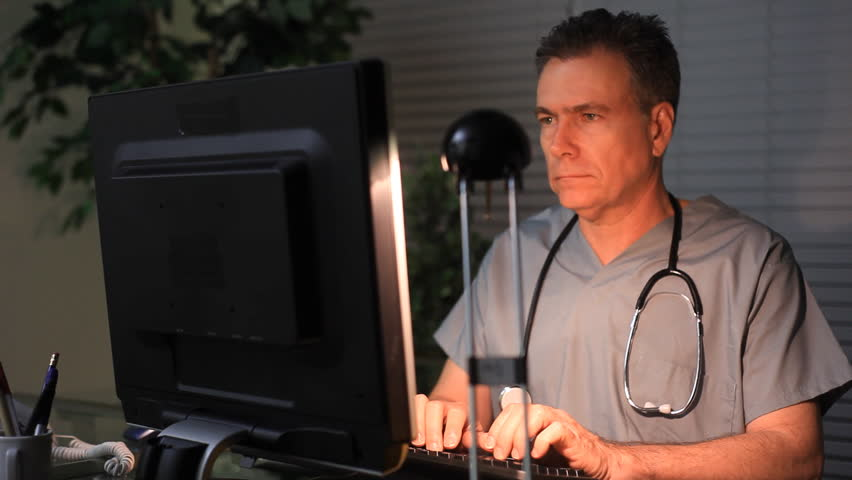 A doctor or surgeon working at his computer late at night.