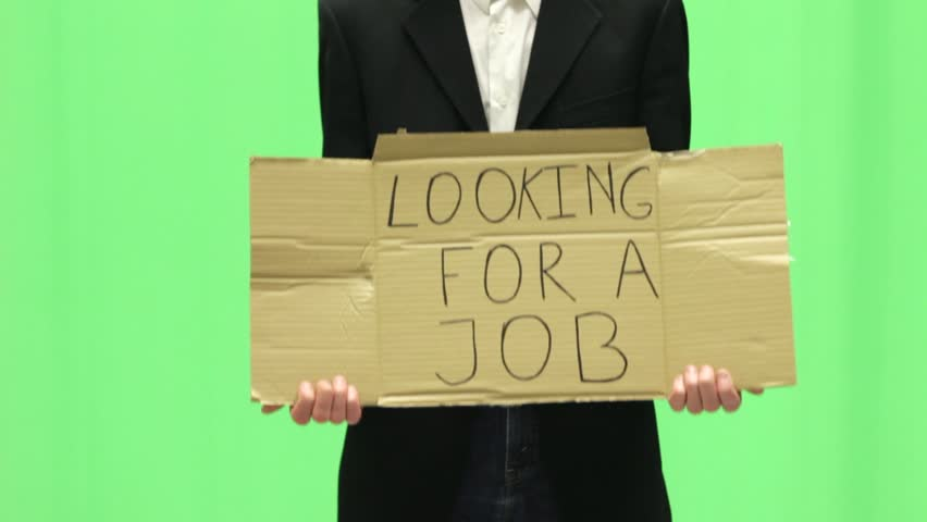 Unemployed young business man with looking for a job sign on green screen