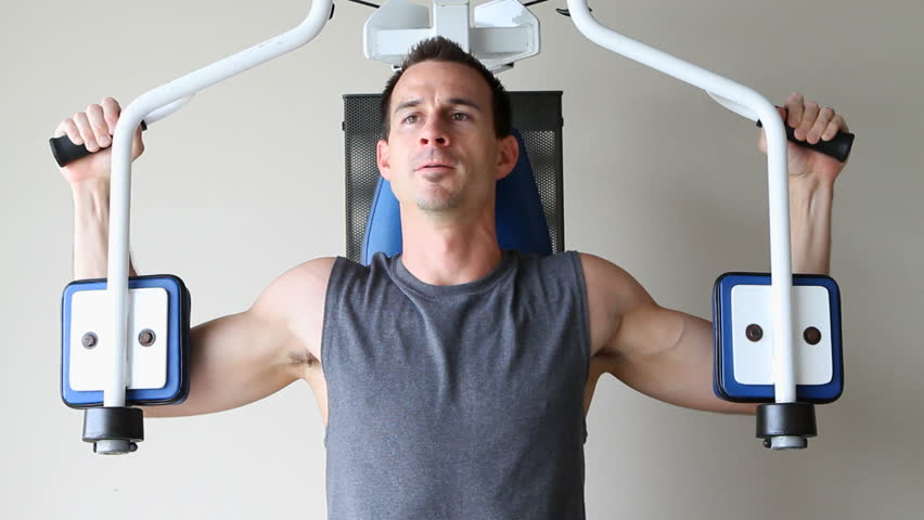 Topless adult male uses a chest exercising machine at