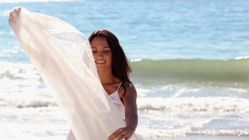 Beautiful woman dancing and twirling her scarf on the sunny beach
