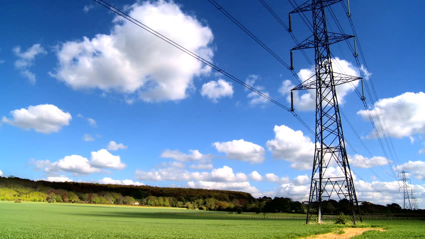 Time-lapse clouds & blue sky behind electricity pylon