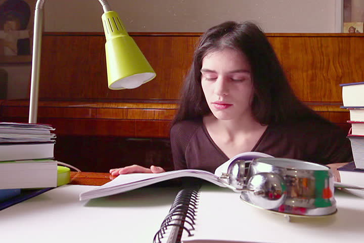 Young adult woman student winds up clock and studies books.