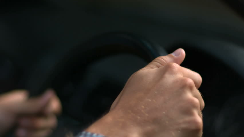Hands of a man driving a car in slow motion
