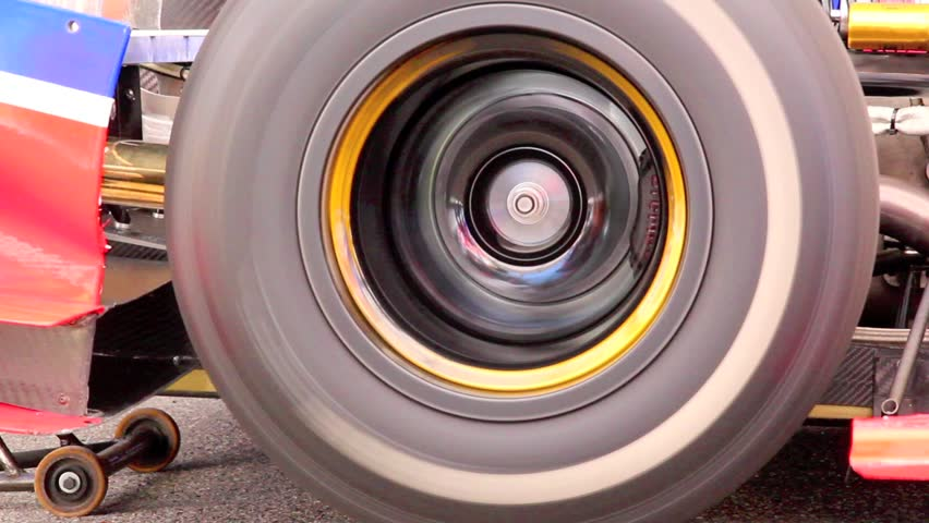 Formula one car wheel, rotating while driver tests engine, inside the garage box