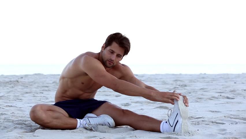 Shirtless man stretching on the beach