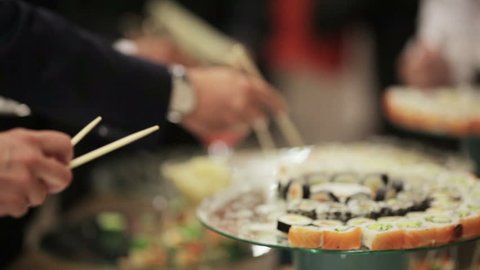 Guests take sushi on a festive cocktail party