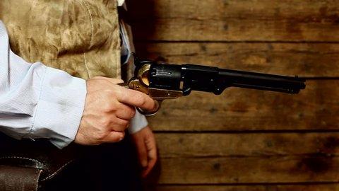 Gunslinger pulls out the gun on wooden background