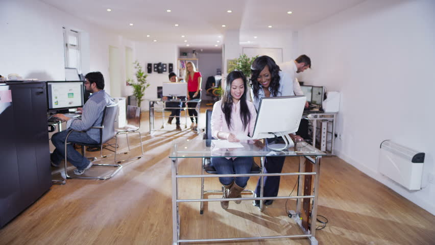 Casually dressed business team are working together in a light and modern open plan office space. Could be a design studio or creative agency.