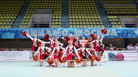 MOSCOW - MAR 24: Performance of undefined cheerleaders team with poms at Championship and Contests of Moscow in cheerleading at Palace of Sports Dynamo, March 24, 2012, Moscow, Russia.