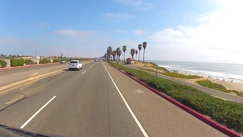 Point of view vehicle shot of car driving the Pacific Coast Highway past North Huntington Beach. This shot features a great view of the jogging path on the beach and the ocean.