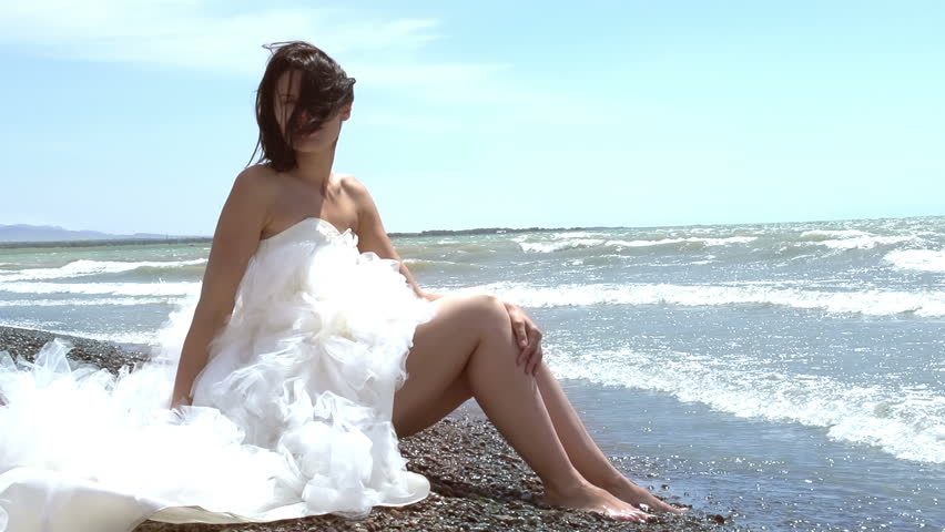Wedding Dress. Beautiful brunette in a wedding dress sitting by the sea. Rolling waves touch the feet. Slow Motion at a rate of 240 fps
