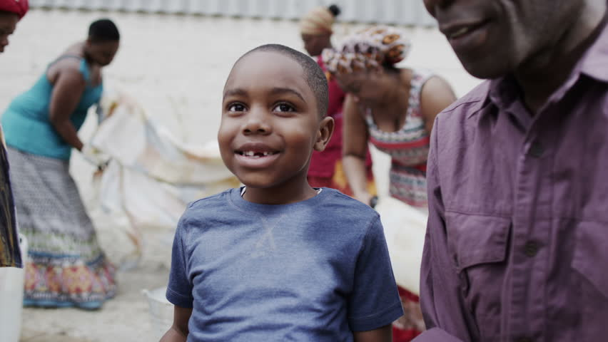 Portrait of happy smiling african boy with his family and community members