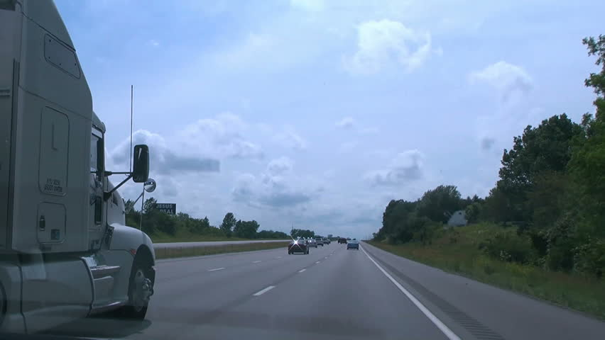 View from the passenger's seat while an 18-wheeled semi tractor-trailer truck passes on the left.