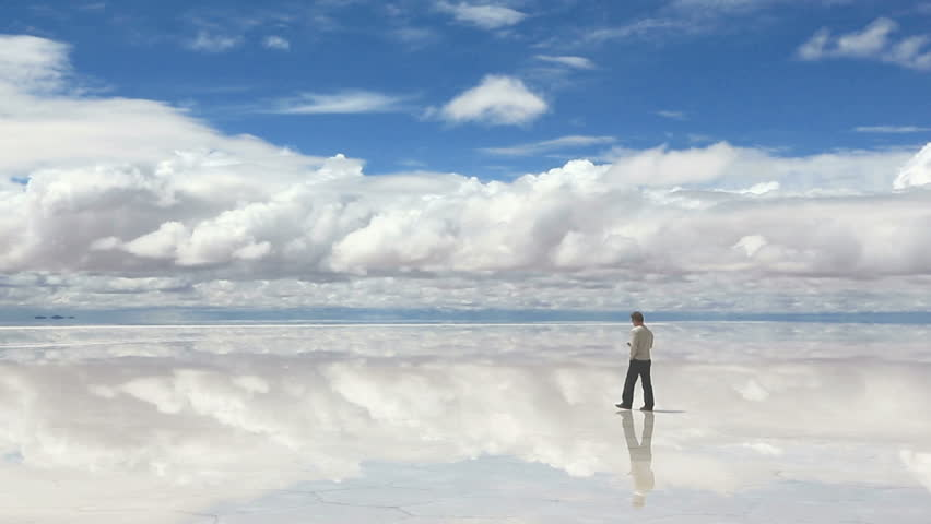 Man talking on the mobile phone in the middle of lake Salar de Uyuni, Bolivia