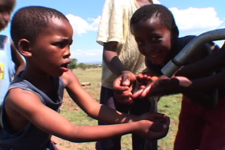 EASTERN CAPE, SOUTH AFRICA - OCTOBER 01, 2005: Boys take turns drinking from the new water pump in village.