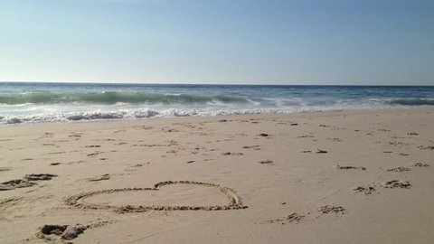 Ocean Waves and Beach: The waves from the sea of beach come rushing to the coast. heart love drawn