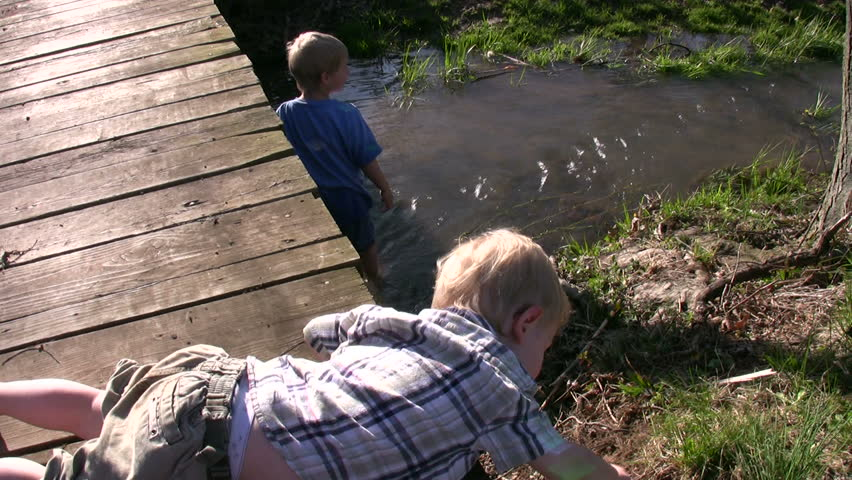 Boys play and wade in flowing creek
