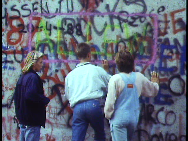 BERLIN - GERMANY - CIRCA - 1988: Berlin, Germany, The Berlin Wall in 1988, medium close up teenagers scrawling graffiti on wall, nice free, me