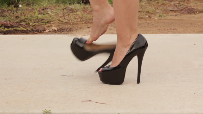 Closeup shot of woman walking in black high heels from frame right, removes heels, then continues walking. Model: Antonella.