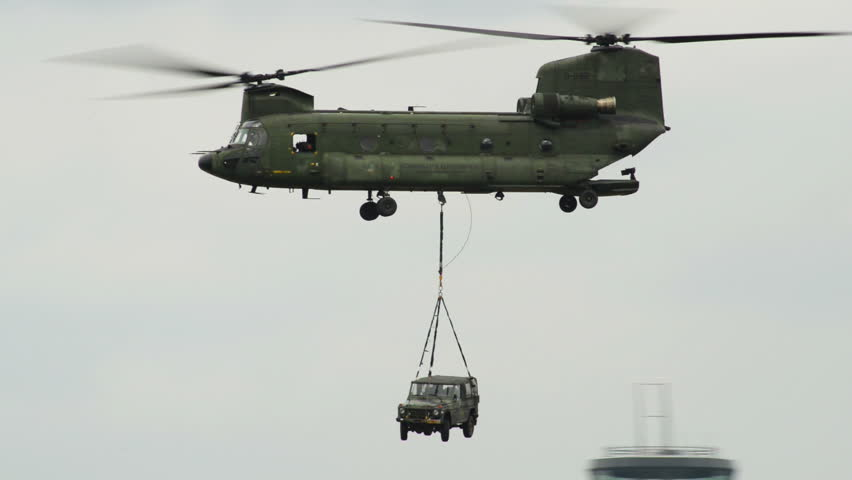 A Chinook CH-47 helicopter carries a car on the hook. 10973