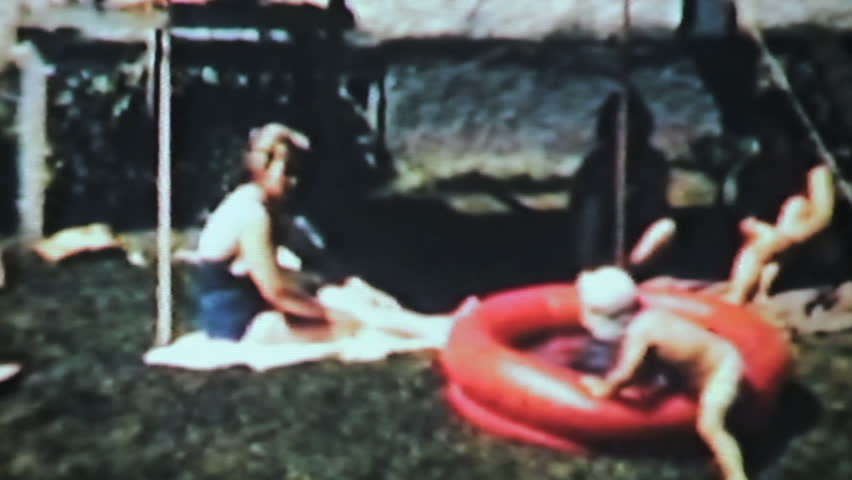 A cute little boy enjoys splashing around in a kiddie pool while his mom, aunt and grandmother look on in 1963.