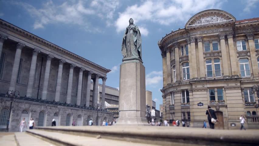 Statue of Queen Victoria, Birmingham, England. Statue of Queen Victoria in Victoria Square, Birmingham. Sunny day. Blurred background people walking around.
