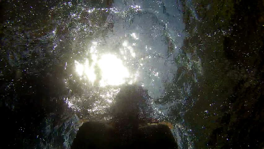 Man swimming underwater in pool