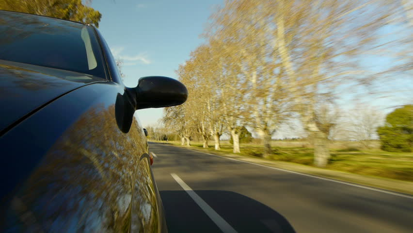 Driving a car, windshield reflection. Hood side reference. Mounted camera, front view. Black car ride. Country road, trees on the side, blue sky, day. Fast Speed / Time-Lapse. HD.  | Shutterstock HD Video #4218442
