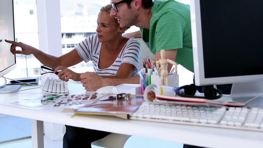 woman showing something to her coworker on creative office