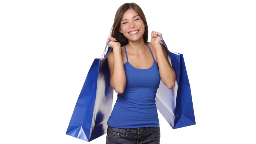 Happy shopping woman excited and cheerful in joyful bliss walking in. Female shopper holding blue shopping bags on white background in studio. Elated beautiful mixed race Caucasian / Asian girl.