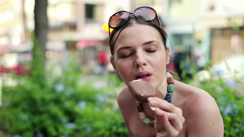 Cute woman eating ice cream in the city, steadicam shot