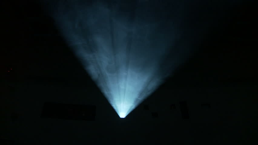 Low, front on view of the light beam of a 35mm projector running in a darkened