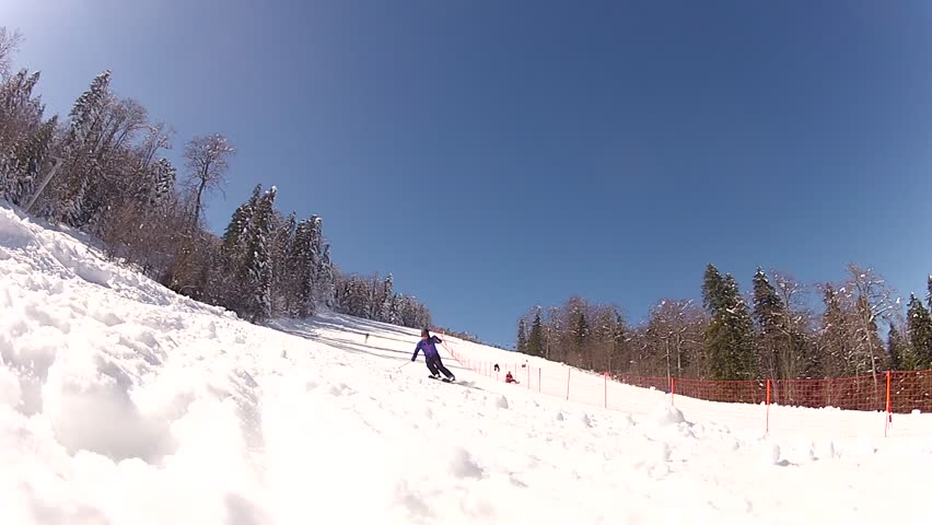 Low angle view of the skiing slope. One person is skiing downhill doing slalom and stops just before the camera, causing the snowdrift to cover it./Skiing Downhill