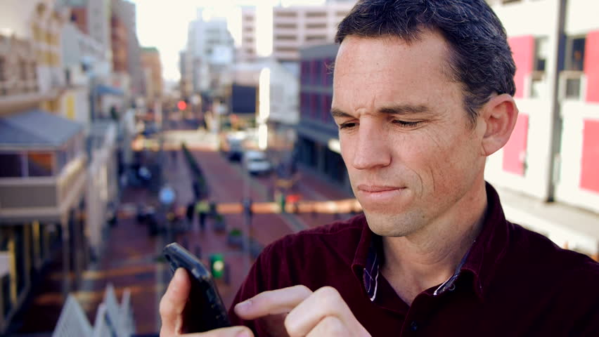 Man in town reading and sending a message on his phone   Shutterstock HD Video #4319627