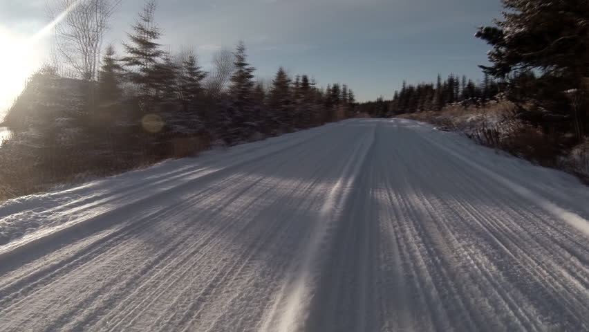 Driving POV on snowy rural Alaskan road near forest