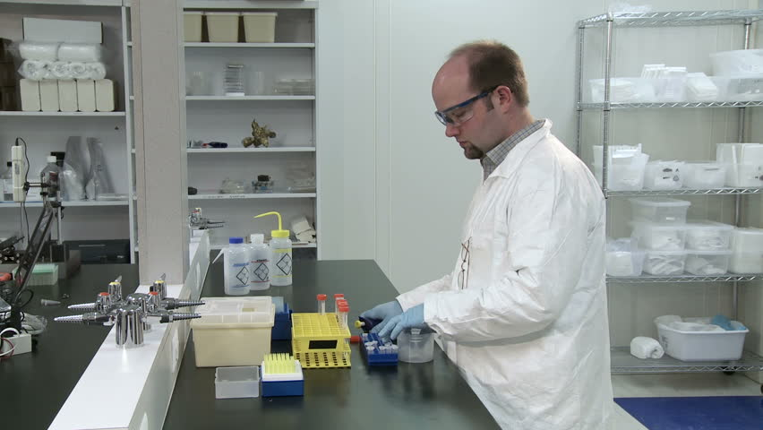 Male Scientist Working In A Laboratory Pipetting Liquid And