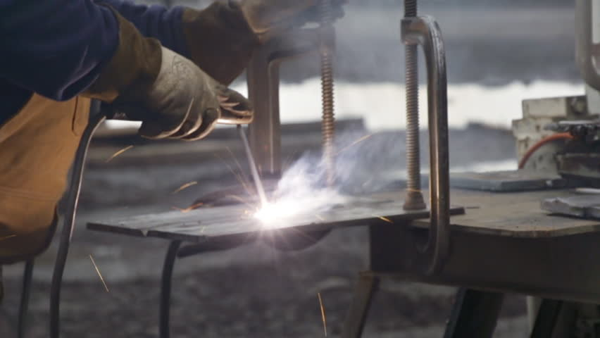 Close-up view of industrial welder joining two plates of steel together