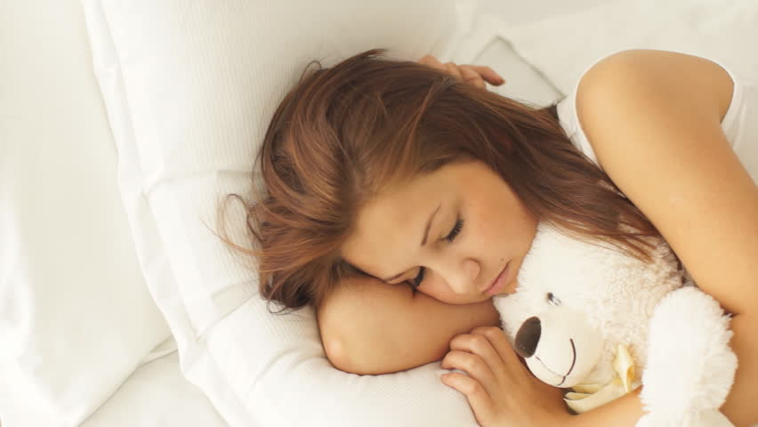 f60ec646c243 Pretty young woman sleeping in bed hugging teddy bear waking up and smiling