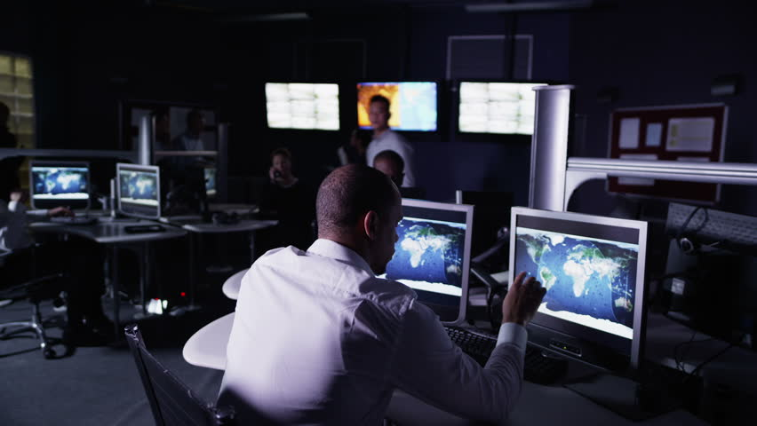 Team of security personnel watching the screens in a system control center. This could be a weather station or airport traffic control room. It could be a police or government surveillance facility. | Shutterstock HD Video #4363334