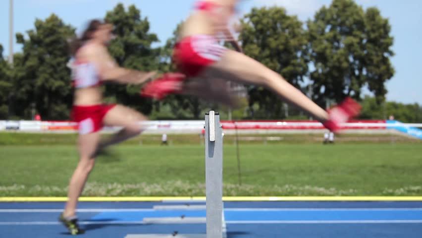 Loop of female hurdle runners leaping over the hurdles