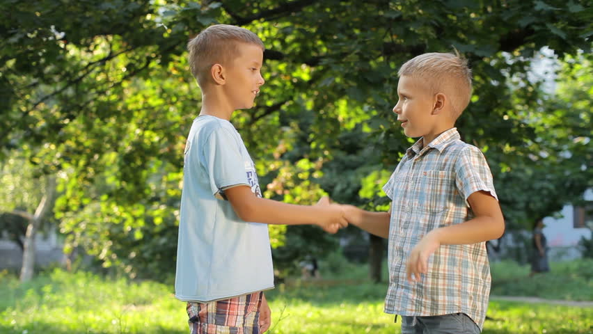 two pleasant young boy introduced in the park during the game. They shake hands and call their names. They are interested