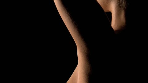 Creative and artistic, tasteful nude shot of a young woman on a black background.