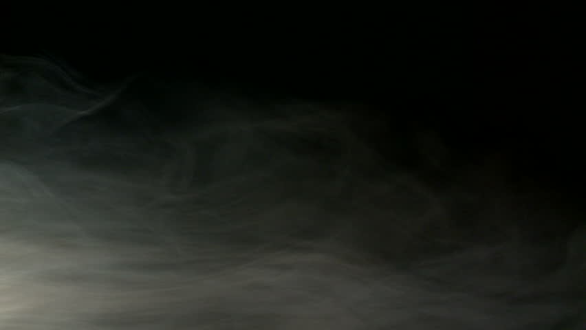 Loopable clip of low-level fog with some swirling vapors against a dark