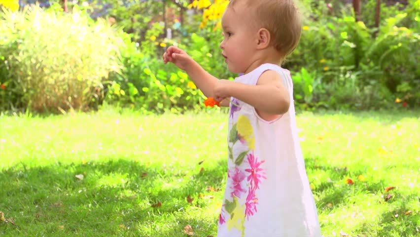 Adorable one year old Baby Girl making her first steps outdoor. Slow Motion Video Footage of the First Steps of the Kid. Sunny day and Green Grass