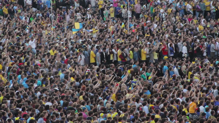 KIEV, UKRAINE - JUNE 16: Football fans on the city square during the Euro 2012 tournament. Crowd of soccer fans raising hands #4417367