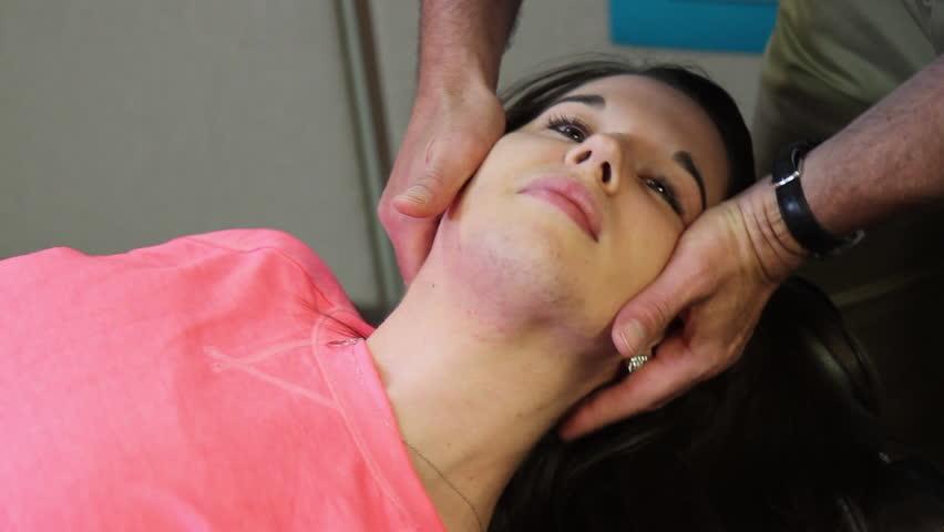 Chiropractor adjusts female patients neck.