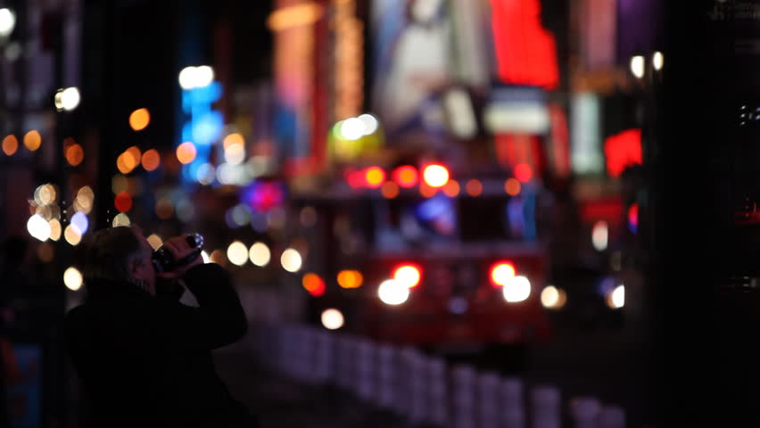 A man filming the Times Square with a small video cam (lighter in original) /