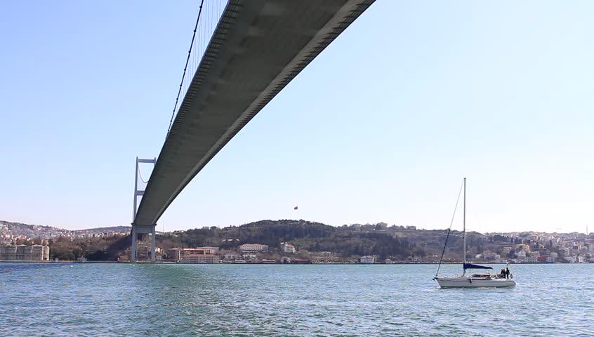 Yacht sailing under Bosporus Bridge in Istanbul