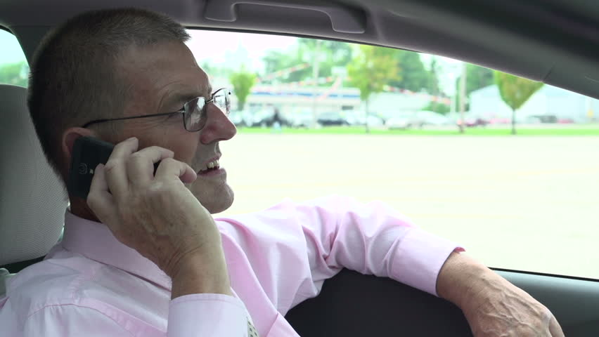 Businessman sitting in car talking on cell phone