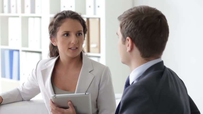 Colleagues having a cheerful discussion in office, woman holding a tablet | Shutterstock HD Video #4434944